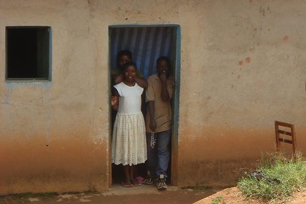Rwandan children looking out doorway