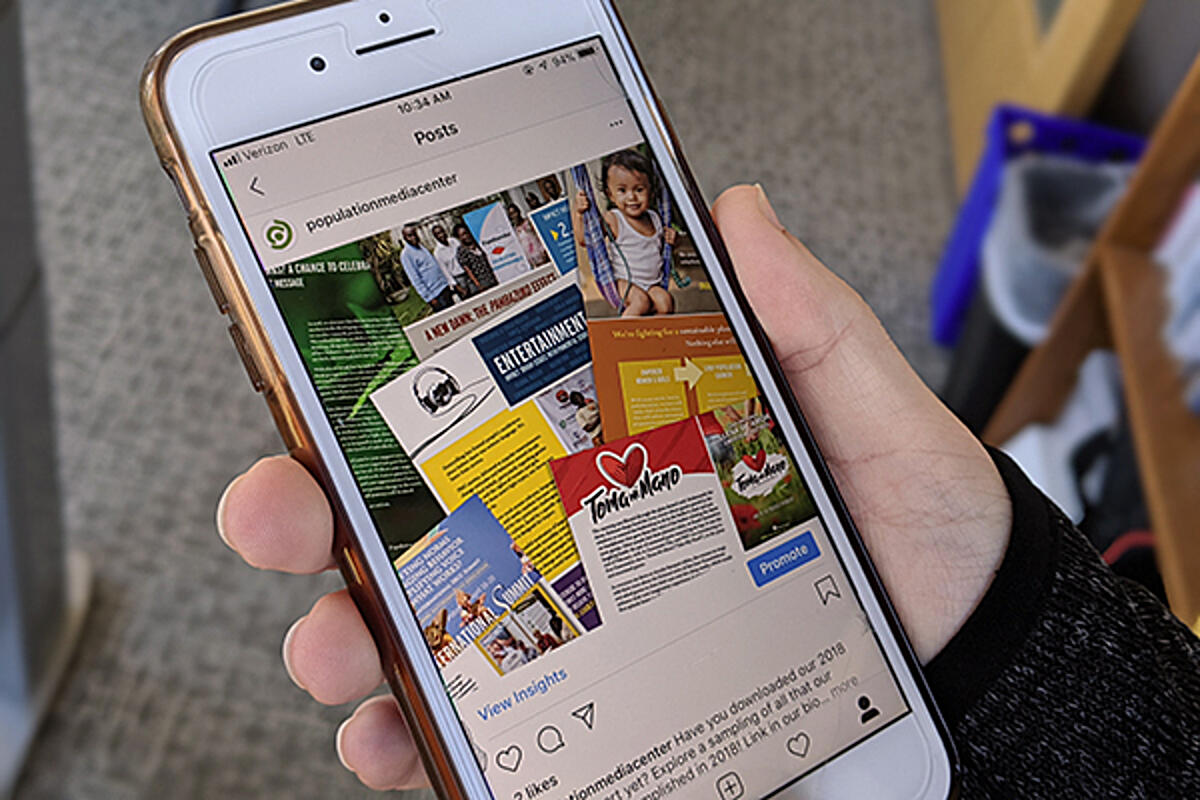 Person holding phone featuring Population Media Center Instagram account