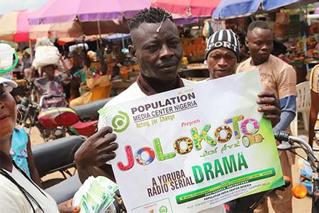 Man holding Jolokoto poster