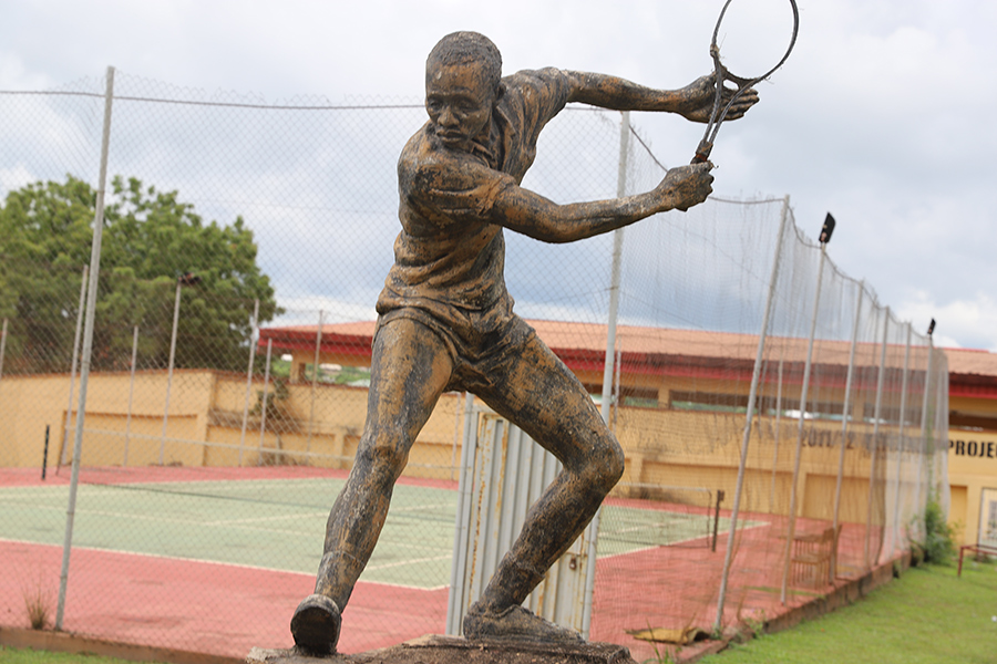 Sculpture of tennis player in front of tennis court