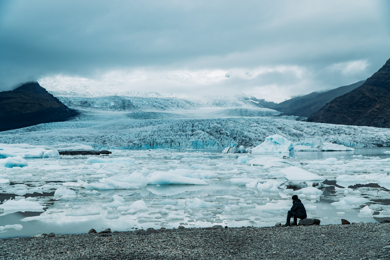 Man sits in front of melting glacier on a grey day.
