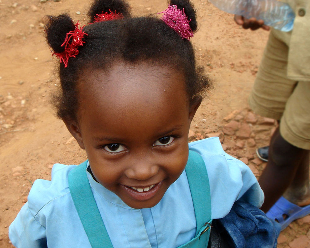 Young Black girl in blue shirt with three little pony tails looking straight up at the camera, smiling.