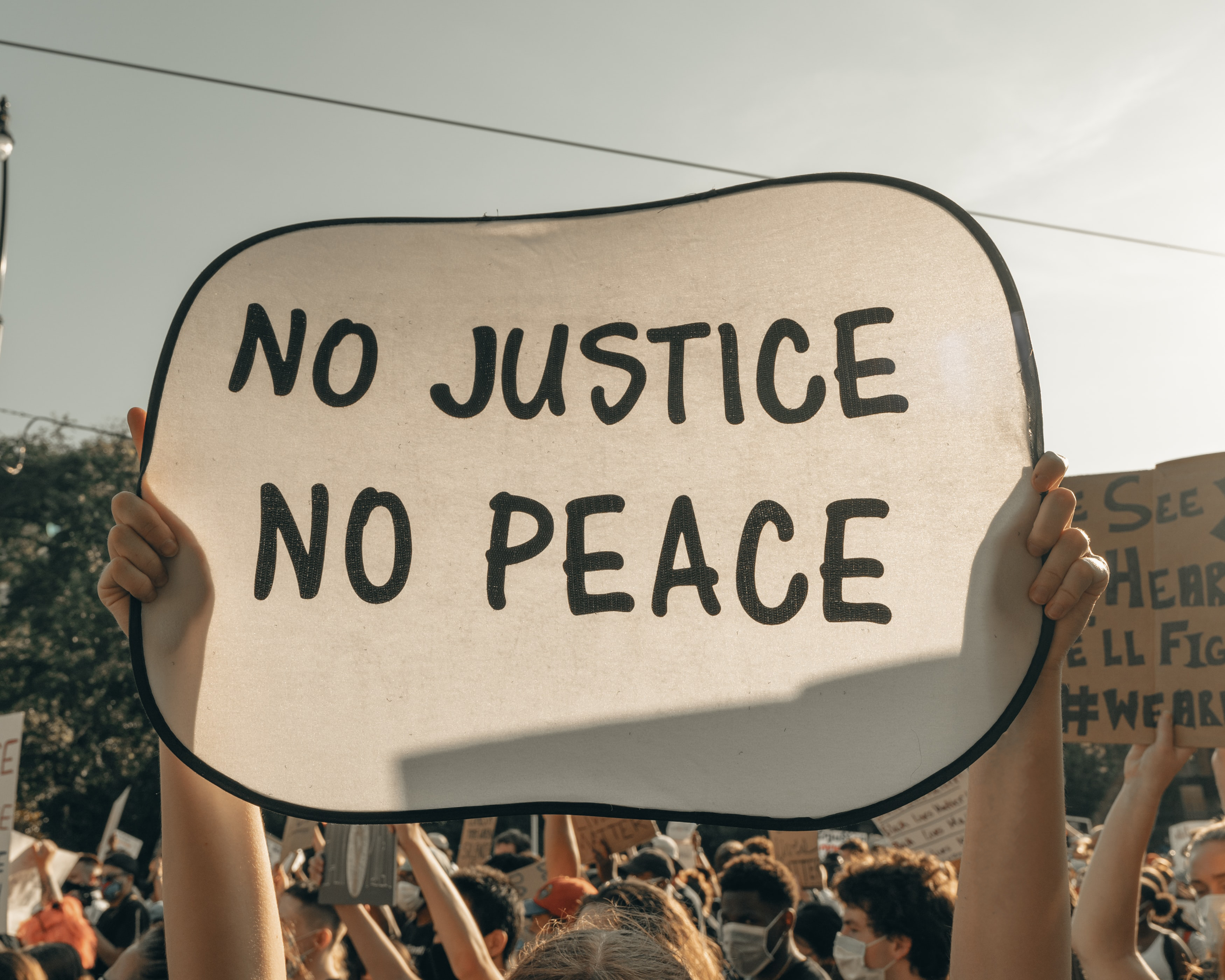 Protester holding sign that says No Justice No Peace