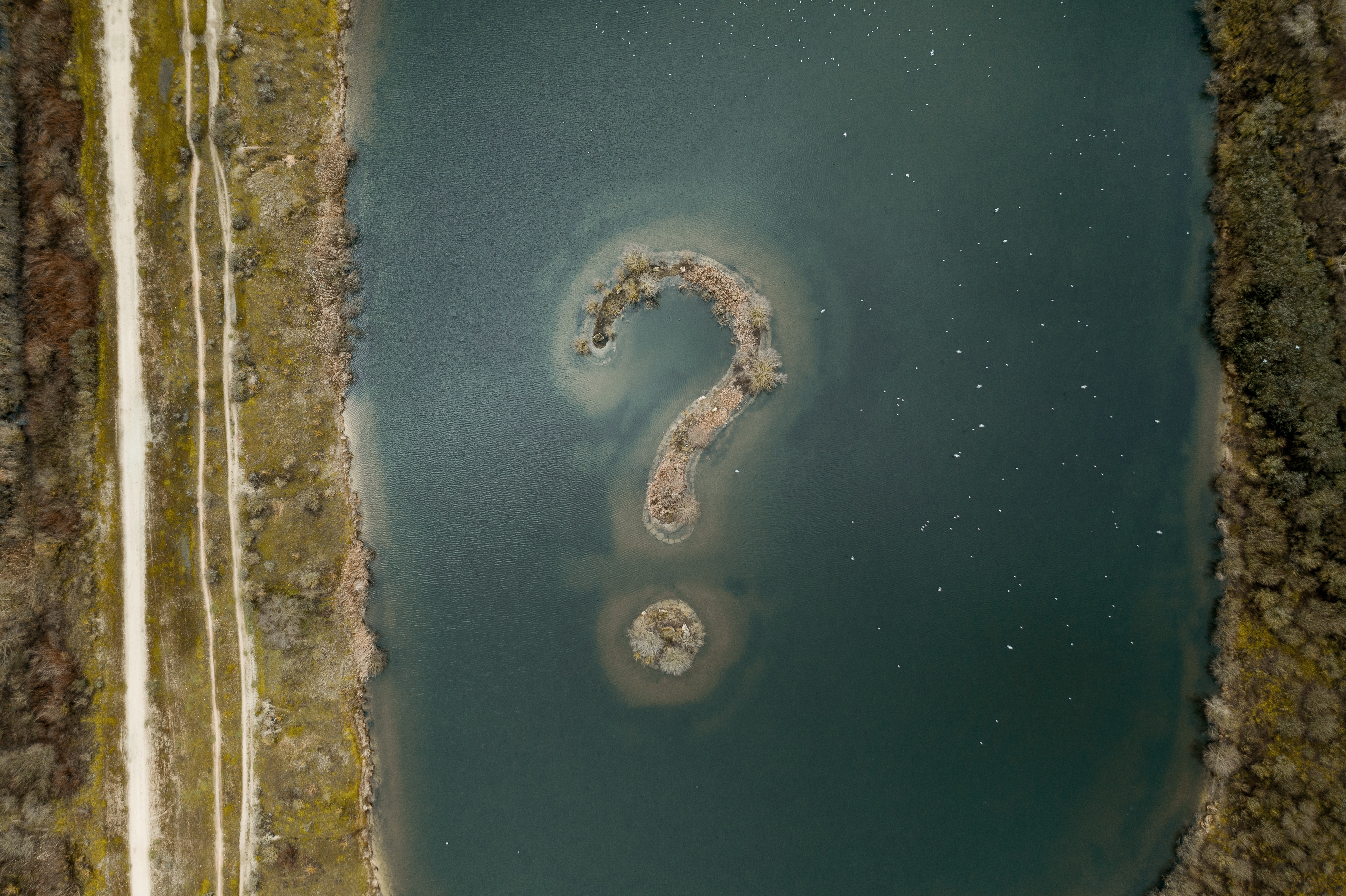Islands shaped like question mark in lake