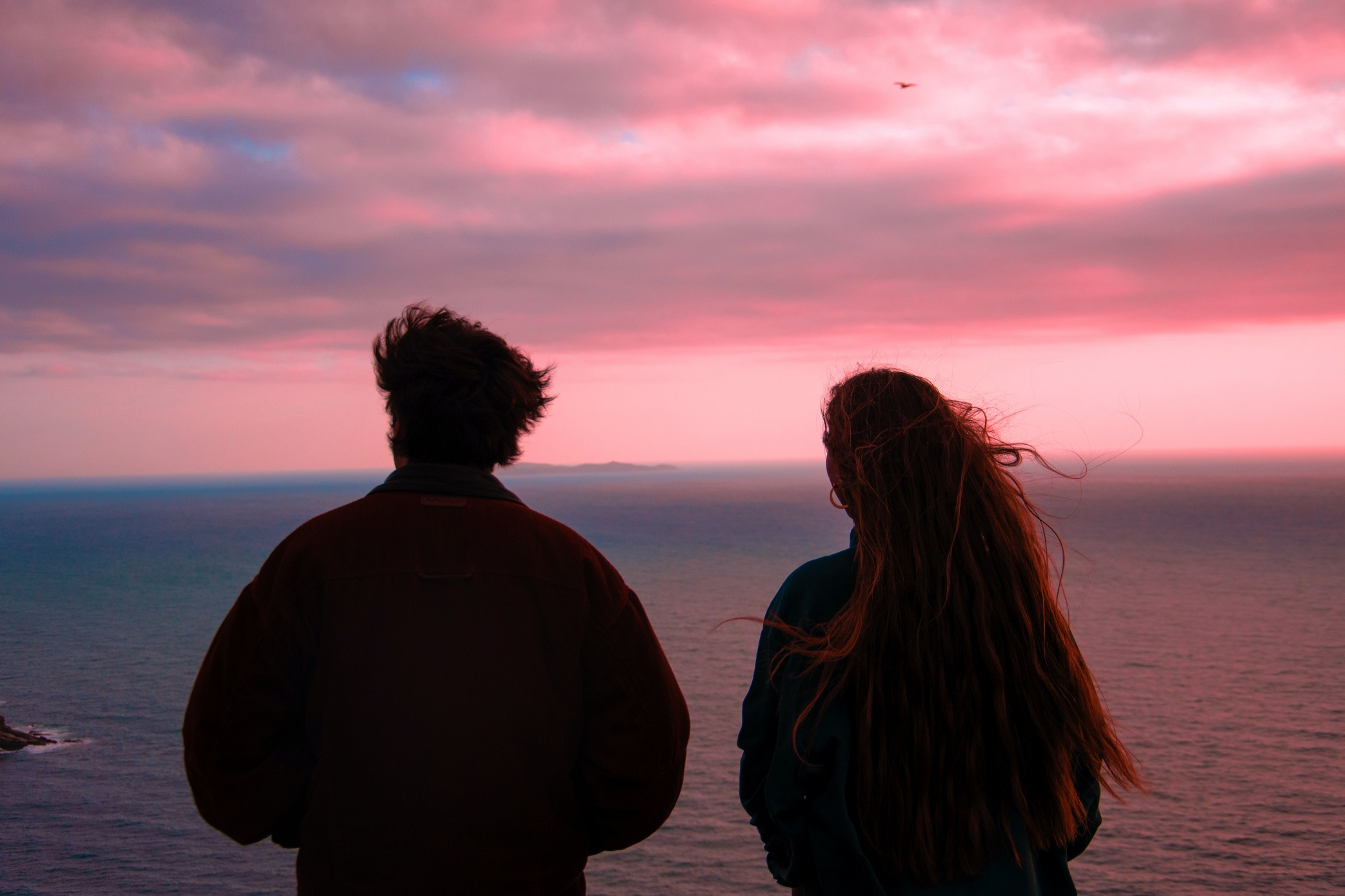 A couple looking out to sea. Photo by Matteo Raw on Unsplash
