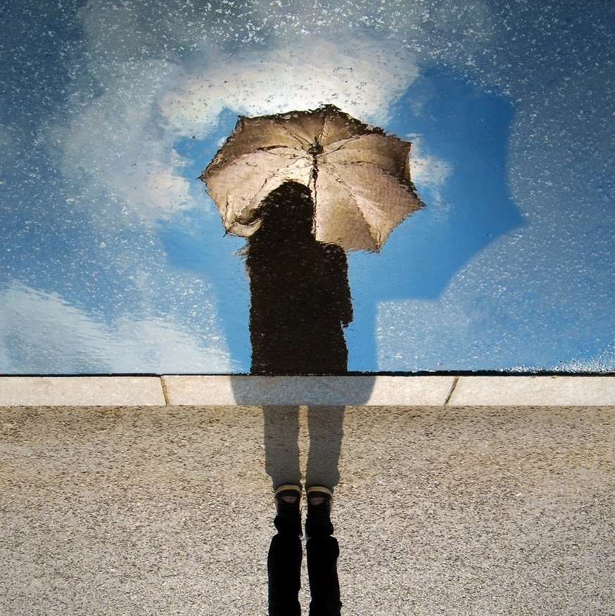 Silhouetted girl holding umbrella